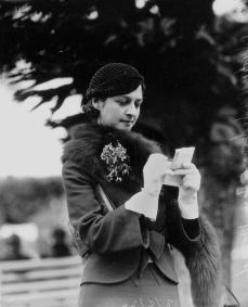 Queensland pianist Audrey Anderson studies the form guide at Ascot races Brisbane August 1933