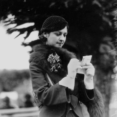 Queensland pianist Audrey Anderson studies the form guide at Ascot races Brisbane August 1933